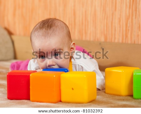 Baby girl plays with toy blocks in home