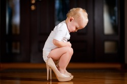 baby girl putting on her mother s shoes and sitting in the hallway in them