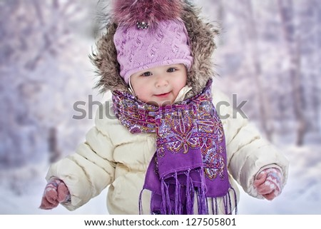 Baby girl's portrait on background of snowy forest