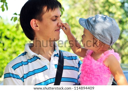 baby girl showing father's nose outdoors