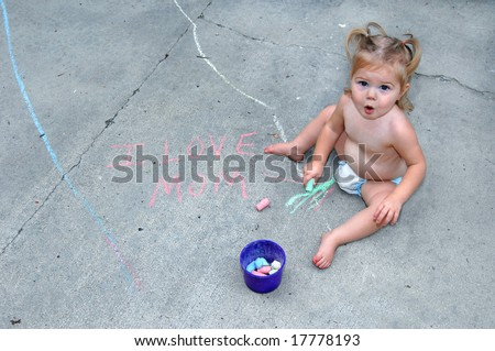 "Baby girl sits on the sidewalk and looks up surprised at being caught writing with  sidewalk chalk.  She has written ""I love mom."""