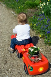 Baby girl sitting in her toy car is pulling a carriage containing a potted plant and Easter eggs kept in a bird's nest