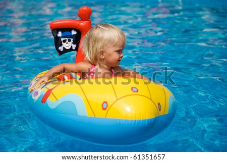 Baby girl sitting in the inflatable boat in the swimming pool.