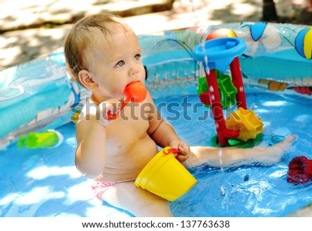 baby girl sitting in the pool on the yard of home