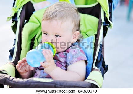 baby girl sitting in the stroller and drinking water