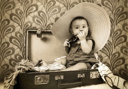 Baby girl sitting into the old suitcase retro image