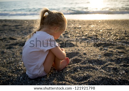 Baby girl sitting on a beach