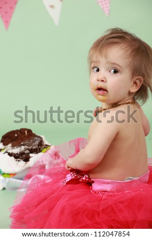 Baby girl sitting on green seamless background behind decorated birthday cake wearing red tutu and bunting flags in the background about to break and smash cake