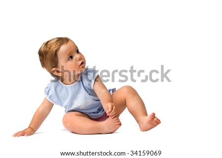 Baby girl sitting on the ground and looking at something with interest, isolated on white background.