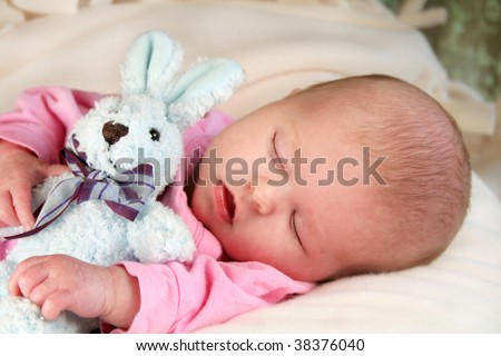 Baby girl sleeping with her arms around a bunny rabbit.