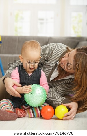 Baby girl smiling holding ball in hands, mum cuddling baby.?