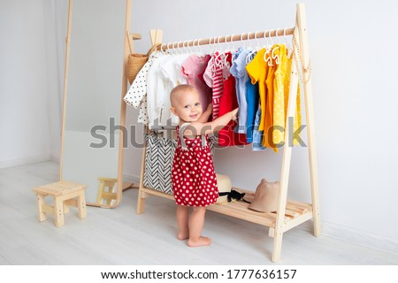 Baby girl stands near a wardrobe and chooses a dress and smiles. Dressing closet with clothes arranged on hangers. Wardrobe of newborn, kids, toddlers, babies full of all clothes. montessori wardrobe.