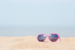 Baby girl sunglasses with pink hearts frame on sea beach sand in hot sunny summer day. Closeup. Front view. Empty place for positive text, inspirational quote or sayings on blue sky background.