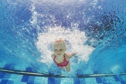 Baby girl swimming underwater and diving in pool with fun - jumping deep down with splashes Active lifestyle, water sports activity and exercising with parents during summer family vacation with child