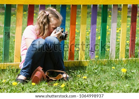 Baby girl taking pictures outdoors.