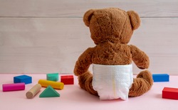Baby girl teddy wearing diaper playing with colorful wooden blocks on pink color floor, wooden wall background, rare view