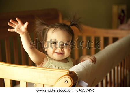 stock photo : Baby girl waving hand and standing up in crib
