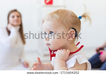 Baby girl wearing a hearing aid. Disabled child, disability and deafness concept. Stock foto ©