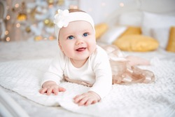 Baby girl wearing cute dress and headband, lies on a white cover in festively decorated room. With surprise watches in the camera, on a background a set of bright fires, soft focus