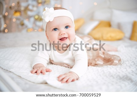 Baby girl wearing cute dress and headband, lies on a white cover in festively decorated room. With surprise watches in the camera, on a background a set of bright fires, soft focus #700059529
