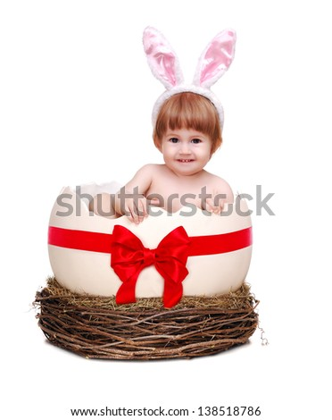 Baby girl wearing rabbit ears hair decoration sitting in decorated with red bow egg shell in nest smiling