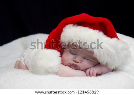 Baby girl wearing red santa hat while sleeping and peeking at times