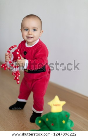 ef91e931cda2f Baby girl wearing Santa's dress and deer's horns behind small Christmas  tree soft toy. First