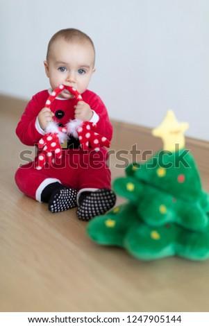 e2df415baeb33 Baby girl wearing Santa's dress biting on deer's horns behind small  Christmas tree soft toy.