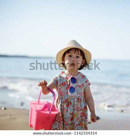 5d0d1844afff baby girl wearing sunglasses running on the summer beach  1142334314