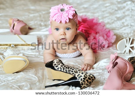 baby girl wearing tutu  laying on the bed with high heels shoes and bags