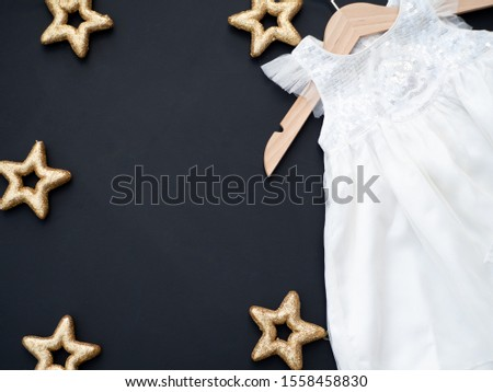 Baby girl white dress on a dark grey background decorated with golden stars.  Baptism invitation idea. Christmas winter theme. New baby announcement concept. Baby shower invitation. Flat lay top view. Zdjęcia stock ©