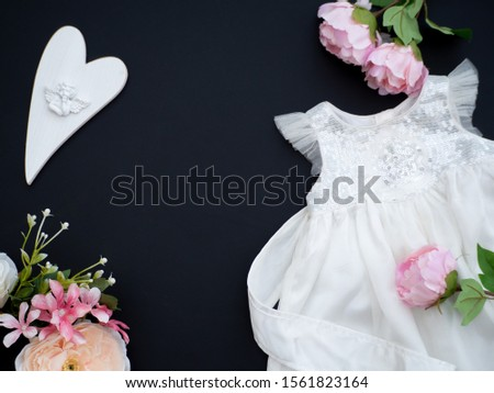 Baby girl white dress on a dark grey background decorated with pink flowers and heart with angel. Baptism invitation idea. New baby announcement concept. Baby shower invitation. Flat lay top view. Zdjęcia stock ©