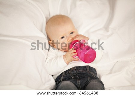 baby girl with a baby bottle lying on a blanket