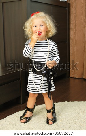 stock photo : baby girl with adult accessories playing indoor