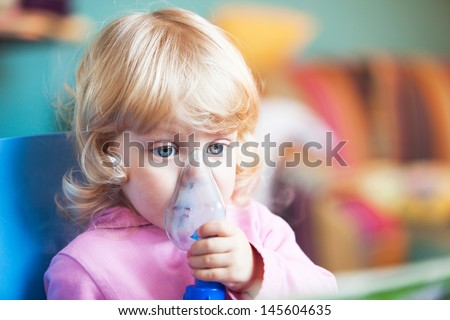 Baby girl with asthma problems making inhalation with mask on her face
