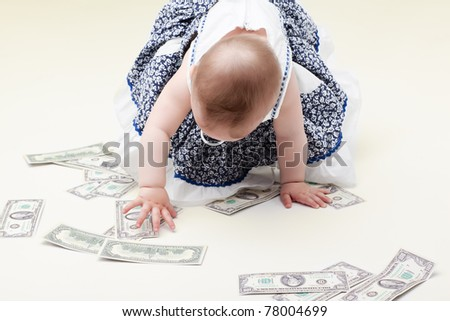 baby girl with pacifier crawling on money