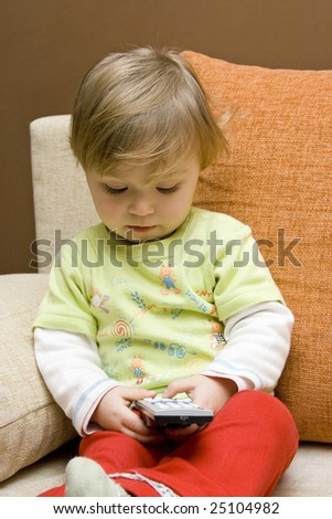 baby girl with remote control on  sofa