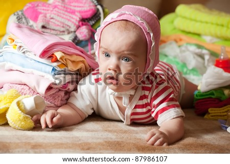 baby girl with stacked of children's clothes