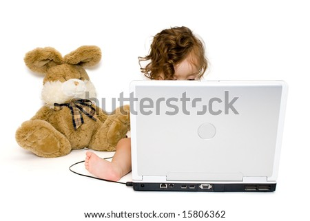 Baby girl working with laptop, toy bunny near her, isolated, on white background