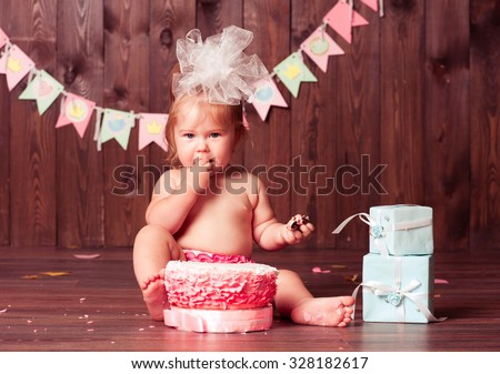 Baby girl 1 year old eating birthday cake in room. Birthday party. Looking at camera. Childhood.
