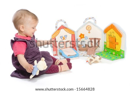 Baby girls sitting on floor playing with stuffed story book. Isolated on white. Toys are officially property released.