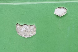 Baby green wall with peeling paint. Two patches of paint are missing showing cement coating and plaster underneath.