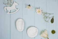 Baby hand and foot print on plaster on blue wooden background, flat lay with flower and toy
