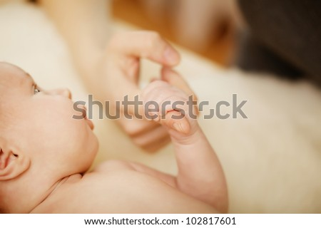 Baby hand holding mother finger