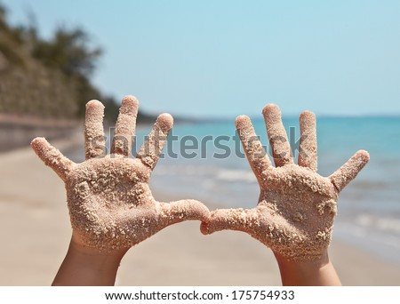 Baby handprints in the sand against sea landscape