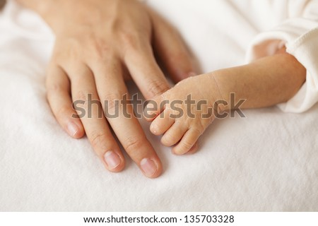 Baby hands and the hands of his mother.