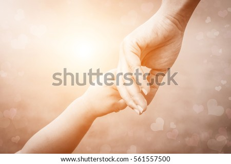 Baby hands holding mother,mom as parent in spring summer day outdoors. Love care newborn daughter in family. Health adult help,support kids accuracy. Abstract blurred heart with rays light background.