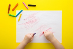 Baby hands holding wax crayons and drawing first scratches lines on white paper on bright yellow table background. Closeup. Toddler development. Point of view shot.