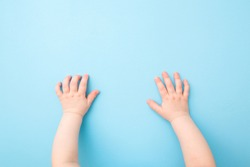 Baby hands on light blue table background. Pastel color. Closeup. Point of view shot.