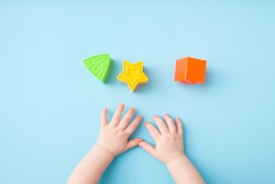 Baby hands playing with green triangle, yellow star and orange square shapes on light blue table background. Pastel color. Closeup. Toys of development for little kids.